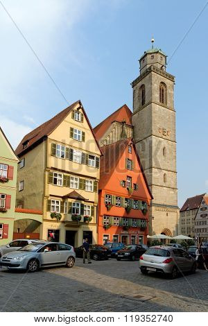 DINKELSBUHL GERMANY - AUGUST 10 2015: Part of the magnificent gabled buildings on Wine Market street and the tower of the beautiful late Gothic church of St. George's Minster.