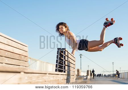 Happy young joyful woman doing a balancing act wearing rollerskates. Young woman in skates jumping with the support of a bench. Beautiful young happy woman wearing roller blades doing a stunt.