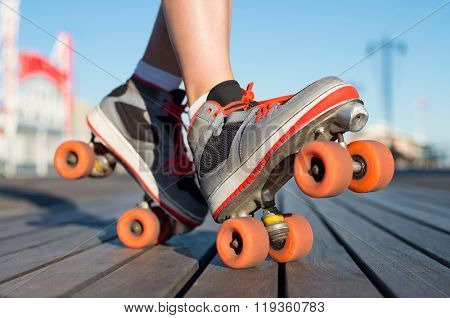 Close up a young woman wearing rollerskates and balancing her legs on toe and heel. Close up of roller skates. Close up of a young woman in roller blade posing outdoor.