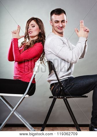 Happy couple having fun and fooling around pretending their hands fingers are guns. Joyful man and woman have nice time sitting back to back. Good relationship. poster