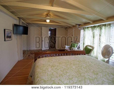 Inside Cottage Bedroom with Queen bed Mounted HDTV White Wicker chairs and bathroom.