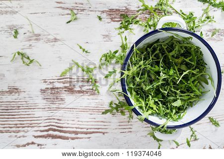 Eruca Sativa, Rucola, Fresh Green Salad Leaves Copyspace Background  Isolated Over The White Rustic