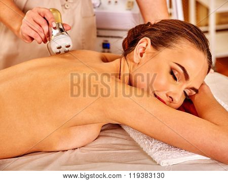 Woman receiving electroporation back therapy at modern beauty salon.  t-shirt