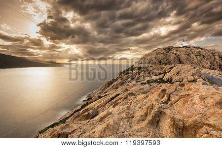 Dark & moody skies over the lighthouse at Ile Rousse and west coast of the Balagne region of Corsica poster