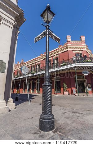 New Orleans, La/usa - Circa February 2016: Pole With Street Signs And Old Colonial House With Ironwo