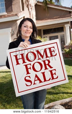 Hispanic Woman Holding Home For Sale Real Estate Sign In Front of House.