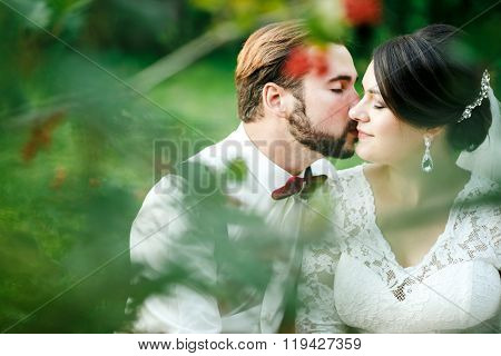 Beautiful couple kissing among spring foliage. Close up portrait of bride and groom at wedding day o