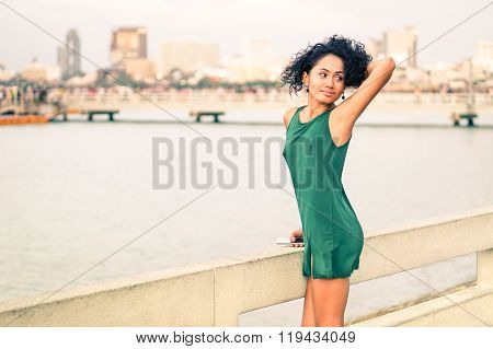 Beautiful Young Woman At Pier Standing In Sensual Posing - Slim Body Latina Girl Holding  Mobile -