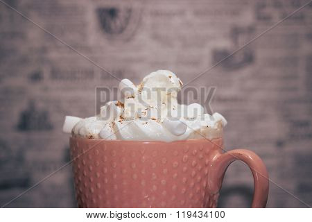 Top part of pink mug with cream and marshmellows