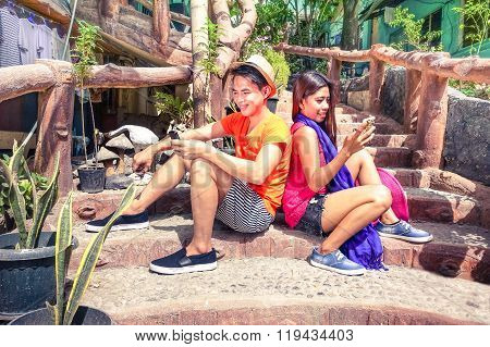 Filipino Young Happy Couple Using Cell Phone Sitting Back To Back - Asian Travel Friends Texting Sms