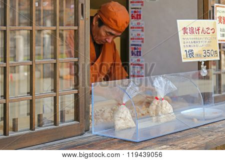 TAKAYAMA, JAPAN - APRIL 2015 : A man selling snack called Genkotsu-ame in Takayama, Japan on April 18, 2015. It's made of soybean powder with Mizuame Japanese sweetener, a specialty of the Takayama