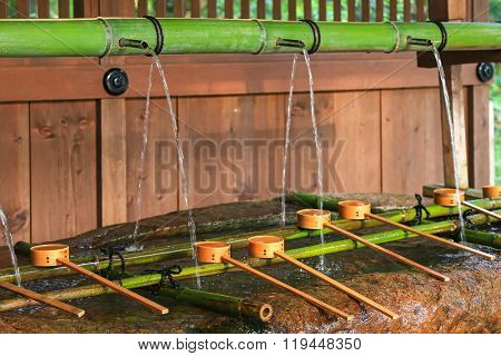 Water running out through bamboo pipe to water basin at Shimogamo jinja in Kyoto, Japan. Water ablution pavilion (Temizuya) is to purify oneself before visiting shrine in Japan