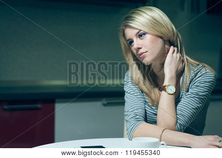 Young woman sitting alone and waiting by the phone on a night kitchen