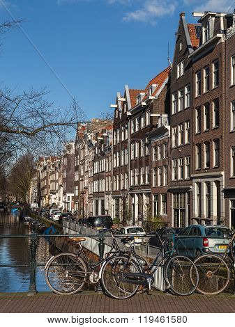 AMSTERDAM NETHERLANDS - 16TH FEBRUARY 2016: A view of buildings along the Amsterdam canals and bicyles chained to the railings.