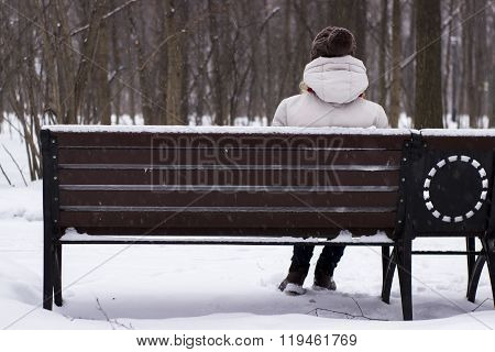 Young beautiful girl sitting on the banch in the winter park
