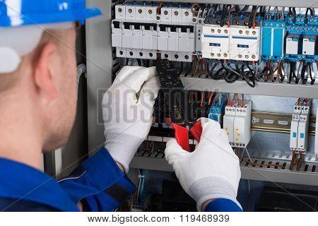 Male Electrician Repairing Fusebox