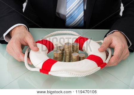 Person Holding Lifebelt With Stacked Coins