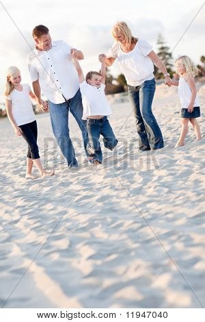 Happy Young Boy Swinging with His Parents and Family at the Beach.