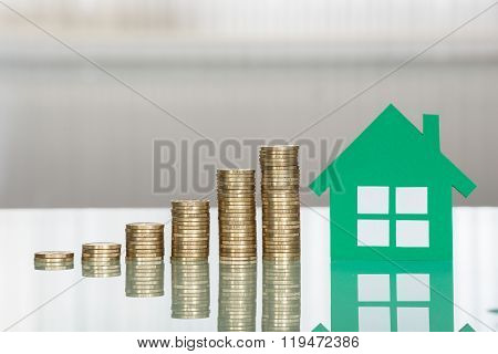House Model With Stacked Coins On Desk