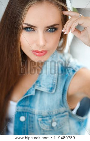 Portrait of young beautiful brunette in the city background