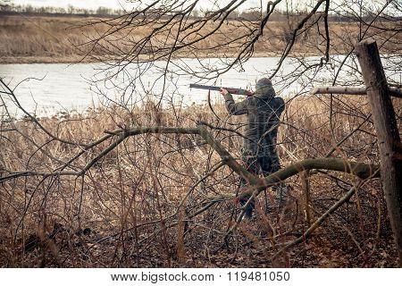 Hunter man with gun aiming and prepared to make a shot during hunt