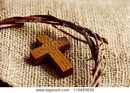 a small wooden cross and a depiction of the crown of thorns of Jesus Christ on a burlap fabric background