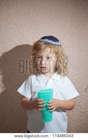 Autumn holiday of Sukkot. Adorable little boy with long blond curls and blue eyes in the Jewish knitted skullcap. He holds the case for the holiday citrus