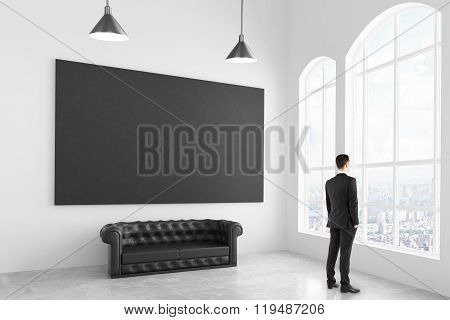 Businessman In Modern White Light Room With Chesterfield Sofa And Blank Black Poster, Mock Up