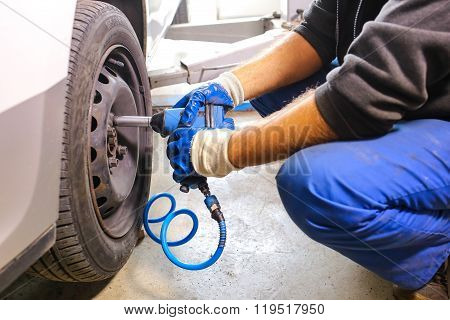 Mechanic unscrewing bolts to change the wheel on a car
