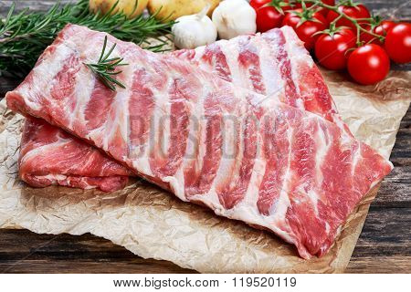 Raw  Pork ribs with a rosemary and vegetables.