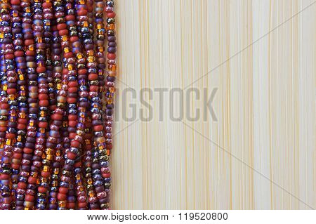 Multicolor beads on wooden bamboo table