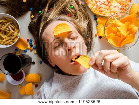Unhealthy concept. Woman with unhealthy food: pizza lemonade chips candy and chips. poster