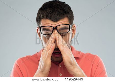 people, eyesight, stress, overwork and problem concept - tired man in eyeglasses rubbing his eyes