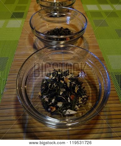 Loose leaf green teas in glasses on wicker table serviette