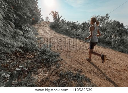 Young woman jogging on the gravel road