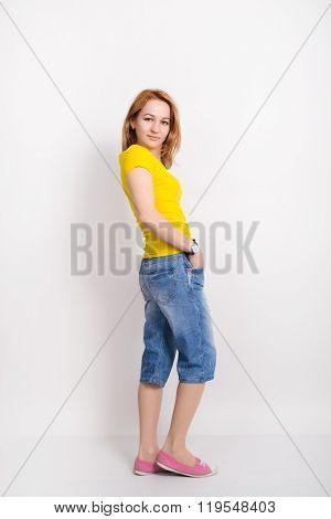 beautiful blonde girl in the yellow shirt, blue breeches posing