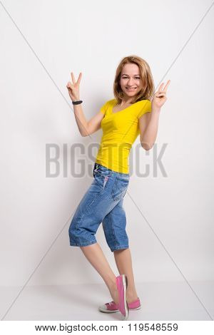 beautiful blonde girl in the yellow shirt, blue breeches shows gesture Victoria