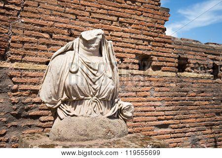 Ancient Roman Statue Set Against A Brick Wall
