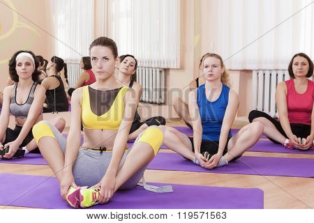 Group Of Female Caucasian Sport Athelets Having Indoors Sport Training On Mats