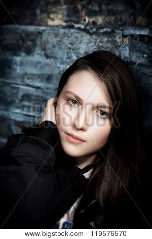 Tween Girl On Blue Brick Wall Not Smiling