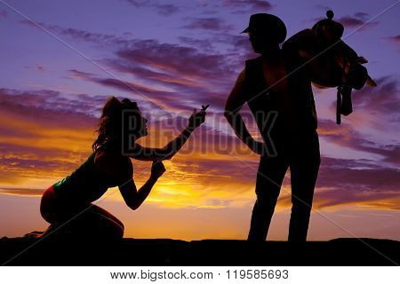 A silhouette of a woman on her knees begging her cowboy to stay.