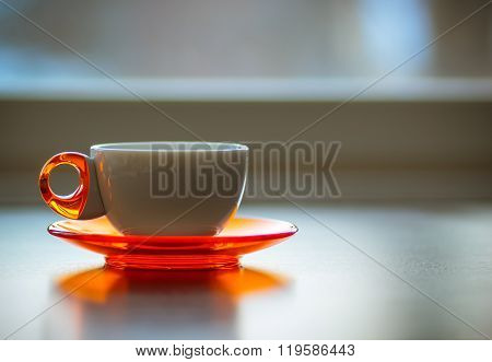 White and orange coffee tea cup on a table with winter view in the back