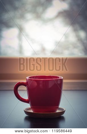 Red coffee tea mug cup in front of a window in a winter day