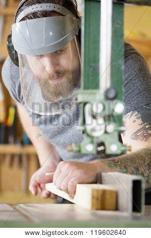 Craftsman with safety mask visor handles band saw in workshop