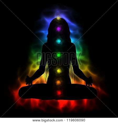 Silhouette of long hair woman meditating - colored chakras