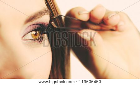 Make up and cosmetics. Woman plucking eyebrows depilating with tweezers. Attractive girl tweezing eyebrows poster