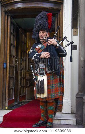EDINBURGH SCOTLAND - MARCH 6: Unidentified Scottish Bagpiper playing music with bagpipe at Edinburgh on March 6 2010. Edinburgh the most popular tourist city destination in Scotland