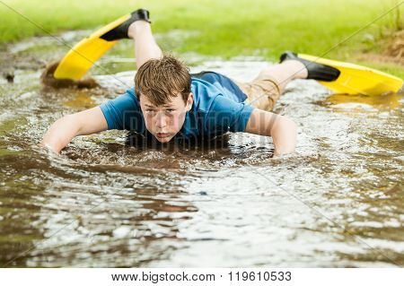 Teenager Trying To Swim In Large Puddle