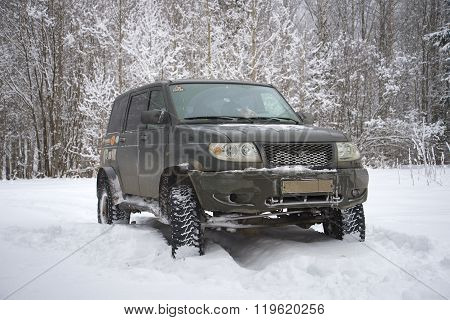UAZ Patriot close-up on the edge of a winter forest cloudy day