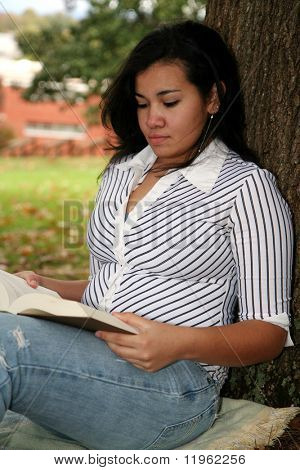 Teenager with studying for a test outside at school